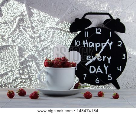 raspberry in a coffee cup with heart and black hours with an inscription