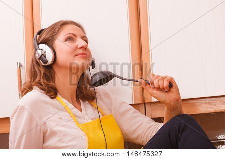 Relax in kitchen. Listening music. Thinking dreaming housewife cook chef with earphones wearing yellow apron sitting and relaxing at home.
