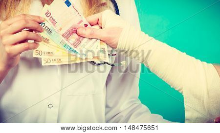 Corruption in healthcare industry. Female doctor bandaging male hand. Man giving money to woman. Bribery in medicine.