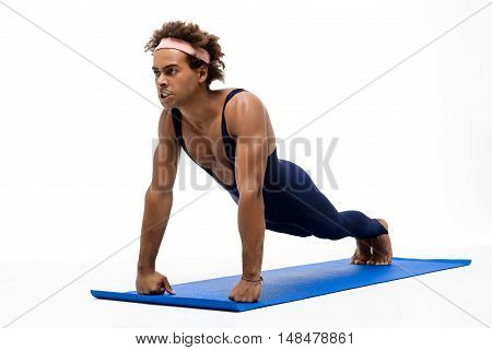 Young handsome sportive african man training on karemat over white background. Copy space.