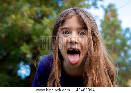 A young girl makes a funny face for the camera. Her eyes are wide open and her tongue is out with her mouth wide open. She is in front of trees and there is copy space.