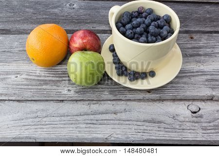 cup of blueberries with an assortment of fruits
