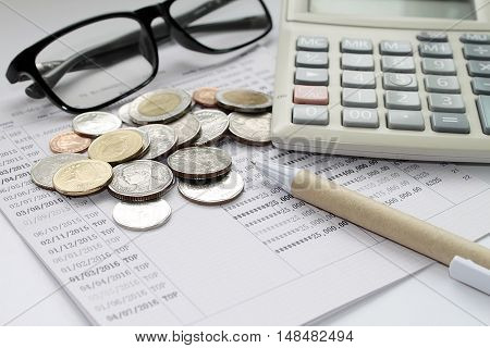 Concept of savings : Coins, glasses, calculator and pen on savings account passbook