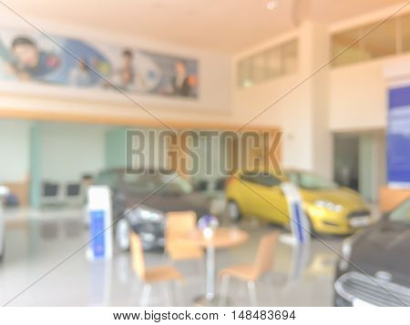 Background blur of car.showroom.Businessmen blur in the workplace.abstract blur background table work in office with car.Abstract background of office shallow depth of focus.