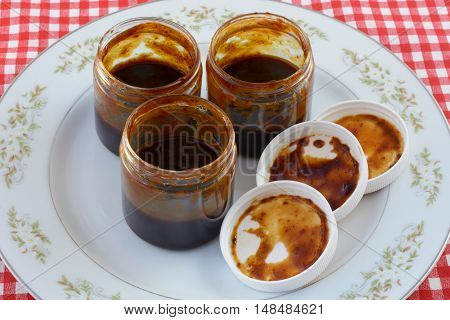 Homemade organic barbeque sauce in jars on plate as part of cooing preparation