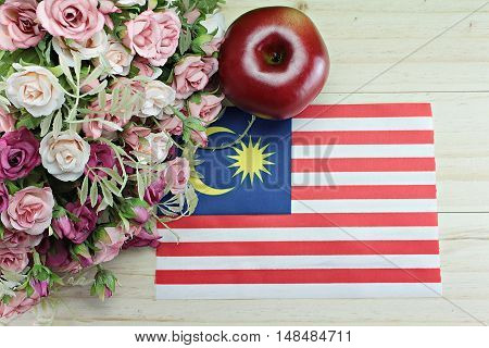 National day : Malaysia flag, apple and flower on wood background