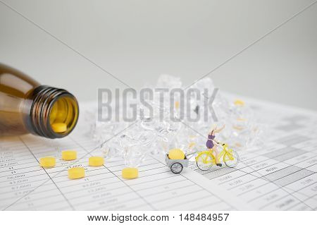 Woman Is Cycling And Carry Yellow Pill On Finance Report
