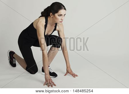 Healthy Young Woman Preparing For A Run Fit Female Athlete Ready For A Spring Over Grey Background W
