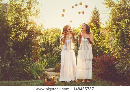Two cute sisters in long white dresses tossed up the harvest of apples and pears. Ripe fruits and vegetables. A bountiful harvest. Agriculture. The setting sun. Soft focus