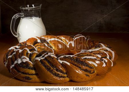 Braided roll with poppy seeds and cinnamon on wooden table
