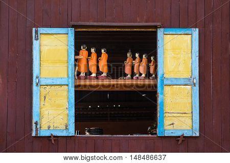 Traditional handicraft monk wooden doll in old window, Myanmar