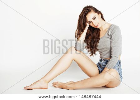 pretty sexy young woman with gorgeous hair in denim shorts and bodysuit posing against white wall long legs
