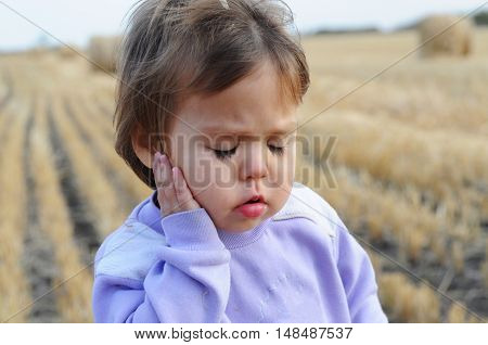 Little Caucasian girl portrait complaining on ache