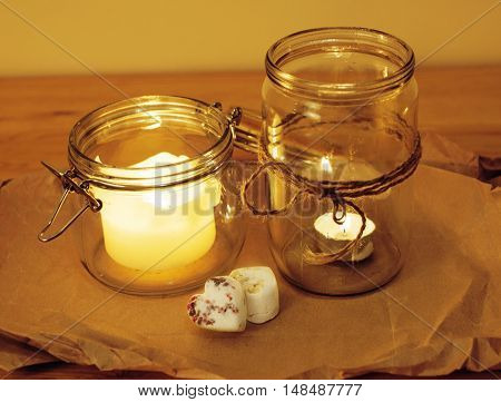 real candles in glass burning romantic celebration concept wooden kitchen close up
