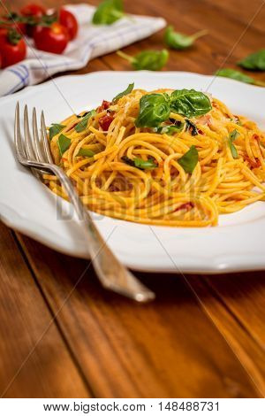 Traditional italian cuisine spaghetti with tomato sauce basil and cheese on wood table