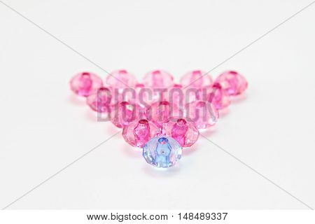 Leadership or teamwork concept : Blue crystal bead leading pink ones, blue crystal bead among pink