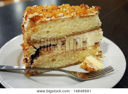 Cake with a piece broken off, on a white plate