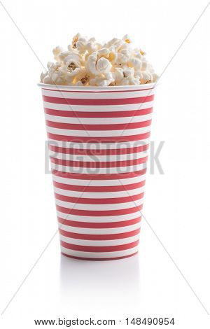 Tasty salted popcorn in striped paper cup isolated on white background.