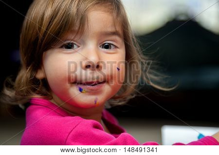 A little girl with a messy face from eating an icing covered dessert looks at the camera with big eyes.