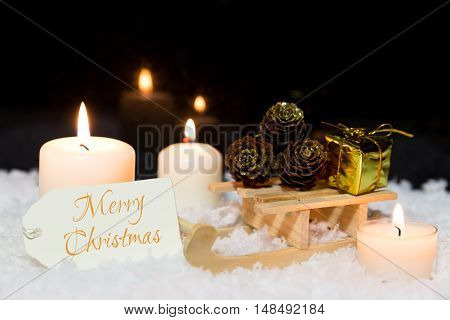 Sledge With Presents, Candles And A Sign In The Snow, Text Merry Christmas