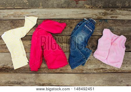 Children's clothing and accessories: jeans, jacket, hair clips and warm vest on old wooden background. Top view.