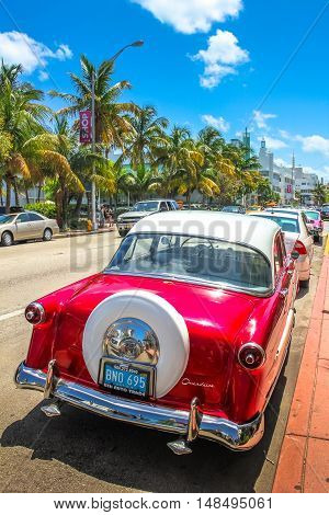 Miami, Florida, United States - April 8, 2012: a 50s classic red vintage car, Ford Crestline, on a street near Ocean Drive in Miami Beach. Miami Beach is famous for its vintage cars.