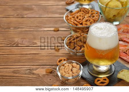 Fresh beer and snacks on a brown background