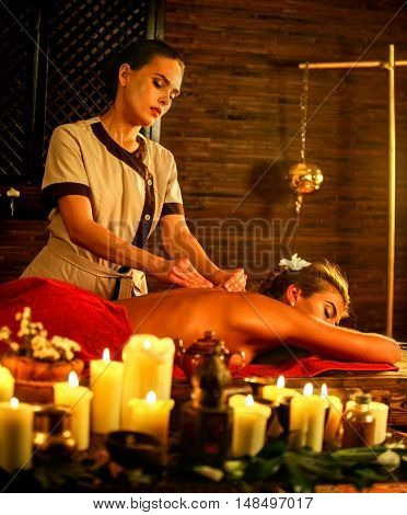 Young woman lying on luxary wooden spa bed. Massage in spa salon with masseuse . A lot of candles background in massage spa salon.