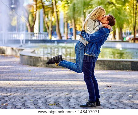 Young couple kissing in autumn park . Loving couple kissing in autumn park. Fountain in autumn park background.