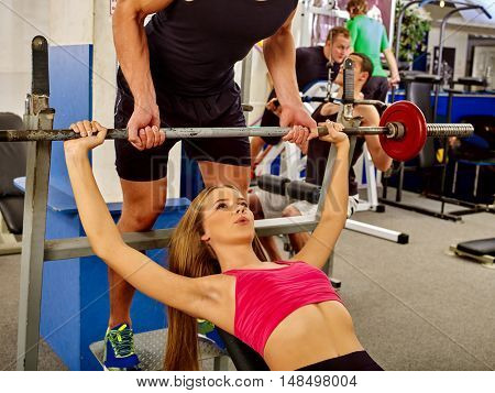 Woman working his arms and chest at gym. She lifting barbell. Man help by woman working barbell.