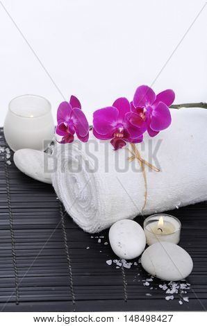 Spa setting on mat with orchid on roller towel,salt