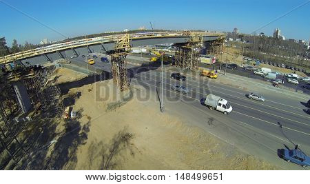 Cityscape with road junction under construction on the highway, aerial view