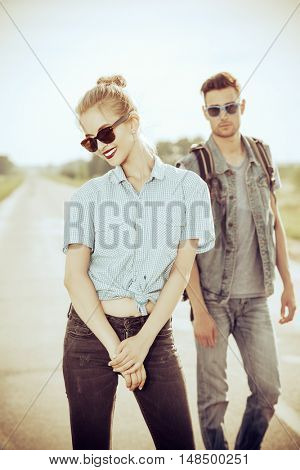 Fashionable models wearing jeans clothes posing on a highway. Denim style. Sepia, retro styled.
