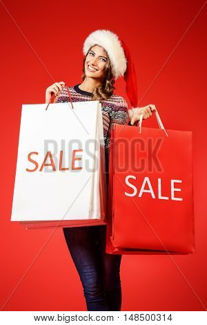 Portrait of a joyful young woman in Santa Claus cap holding shopping bags over red background. Christmas.