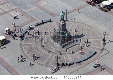 Adam Mickiewicz monument at the Main Market square with walking people. Aerial view from St. Mary Cathedral tower.