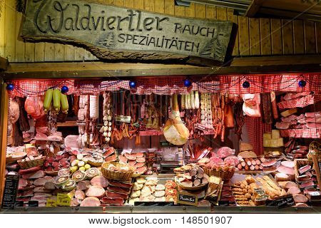 VIENNA AUSTRIA - NOVEMBER 21 2013: Christmas Market at Rathausplatz. Kiosk selling huge selection of traditional meat products.