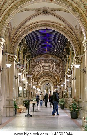 VIENNA AUSTRIA - NOVEMBER 24 2013: People strolling along the exclusive shopping arcade - Freyung passage built in the 19th century as part of the Ferstel Palace.