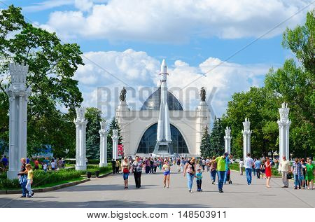 MOSCOW RUSSIA - JULY 23 2016: Unidentified people walk along alley with view of pavilion