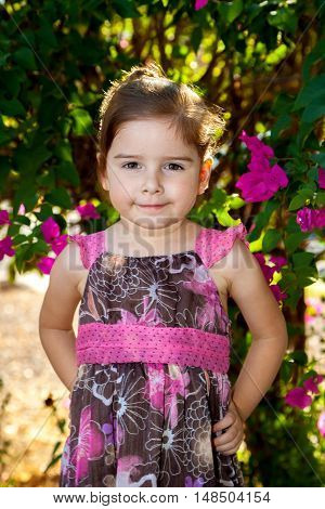 An adorable little girl in a pink and brown floral dress looks confidently at the camera with hands on hips and a smirk on her face.