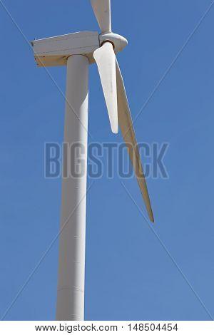 Wind turbine over a blue sky. Clean alternative renewable energy. Vertical