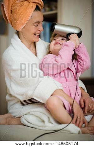 Mother and her little child in bathrobes having while drying hair
