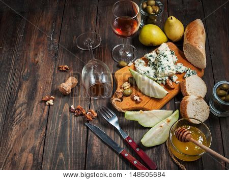 Blue cheese with honey, olive and pears on rustic table. Wine glasses.