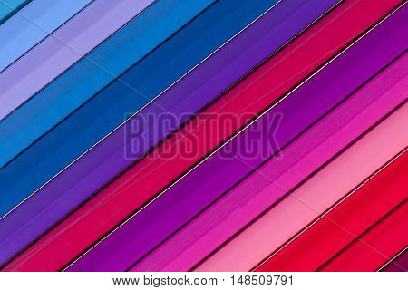 Background of parallel colorful pencils slant close up