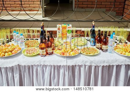 MOSCOW, RUSSIA - MAY 30, 2015: Holiday table full of bottles of wine, juice, water and snacks on plates.