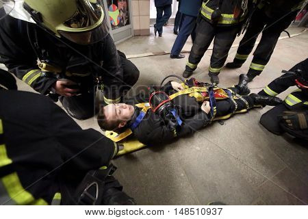 RUSSIA, MOSCOW - FEB 26, 2015: Suffer is laying on the hand-barrow with oxygen mask at Preobrazhenskaya ploshchad subway.