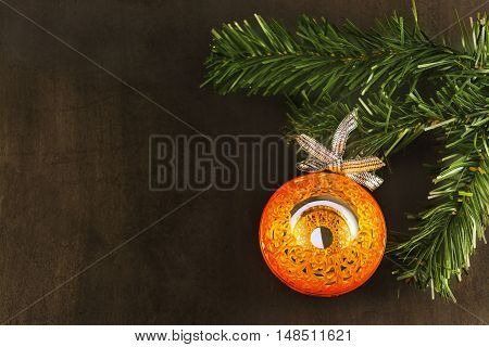 Big orange shiny mirror ball on new year tree on a black background.