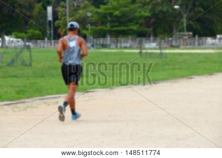 Blur blurred abstract young man jogging in the park rear view