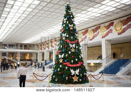 MOSCOW, RUSSIA - DEC 17, 2014: Security guard and other people walk in large hall with Christmas tree in Kremlin Palace.