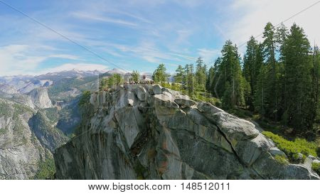 CALIFORNIA - OCT 23, 2014: People watch landscape from top of rocky mountain in Yosemite National Park at autumn sunny day. Aerial view. Park total area is 3081 sq. km.