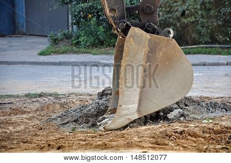 Excavator bucket with building sand in the works close up.